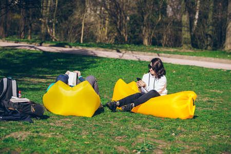 couple laying on yellow inflatable mattress in city park. reading book. taking selfie. leisure time