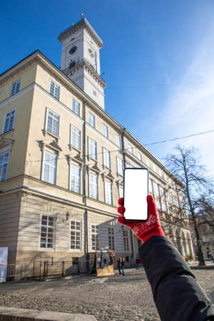 woman hand in red gloves holding phone with white screen lviv city hall on background copy space travel concept
