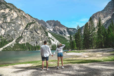 couple standing looking at lake in mountains. summer time