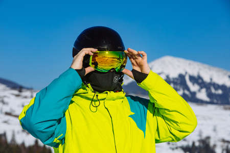 man in helmet and ski mask. reflection. winter activity. sunny day