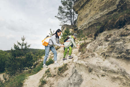 young woman with little toddler boy climbing by rocks. copy space