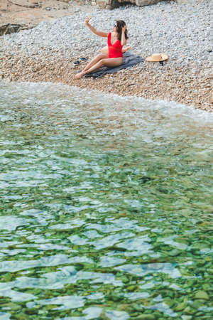 young pretty woman in red swimsuit sitting at rocky beach with phone taking selfie picture sea summer vacation Archivio Fotografico - 150760234