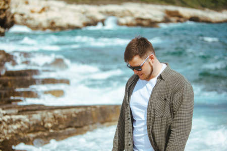 young man in sunglasses with beard portrait at seaside. summer vacation