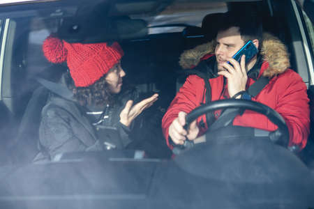 couple in car in winter outfit driving and talking rent a car