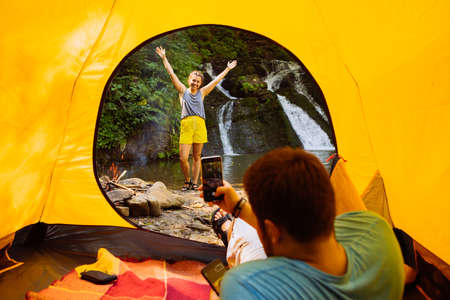 man taking picture of young woman on phone from yellow tent. waterfall on background. summer activities