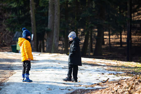 two boys in winter clothes walking by snowed park. view from behind
