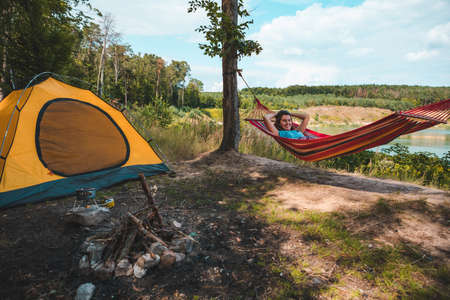 woman laying on hammock at camp near lake summer hiking concept copy space travel concept