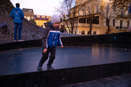 little boy playing outdoors in autumn clothes