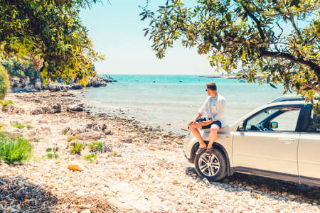 man with coffee cup standing near car at sea summer beach vacation concept