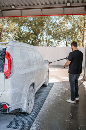 strong man washing car at self carwash outdoors