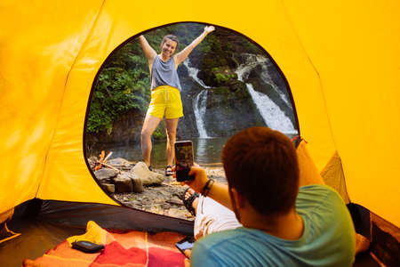 man taking picture of young woman on phone from yellow tent. waterfall on background 스톡 콘텐츠