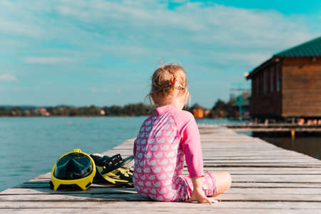 little girl at wooden pier at summer lake