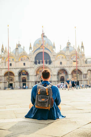 young man sitting on the ground looking at cathedral saint marco church