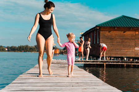 young smiling woman with little girl kid at wooden pier at lake beach. summer time 스톡 콘텐츠