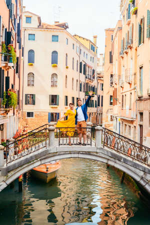 couple standing on the bridge crossing venice canals