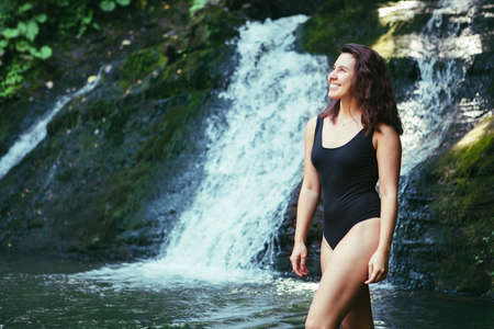 gorgeous woman in sexy black swimsuit in front of waterfall