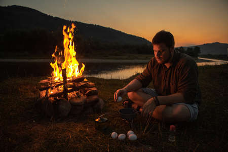 man sitting near bonfire cooking fried eggs