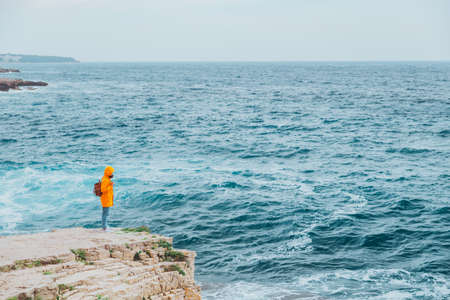woman in yellow raincoat with backpack standing on the cliff looking at inspirited sea Banco de Imagens
