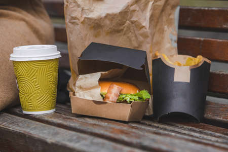fast food. big burger with cup of tea on a bench. Stock Photo