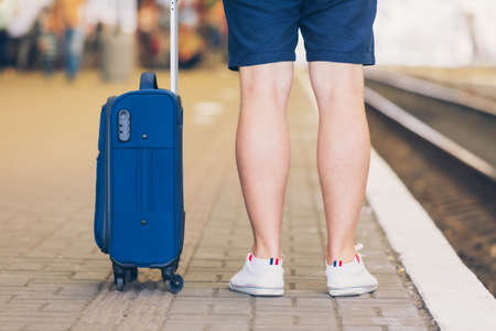 man with suitcase on wheels standing on railway station platform travel concept 免版税图像