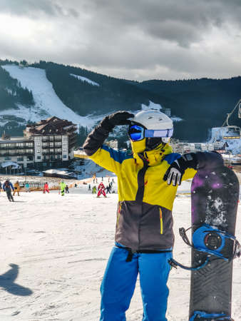 woman standing at ski resort hill with snowboard