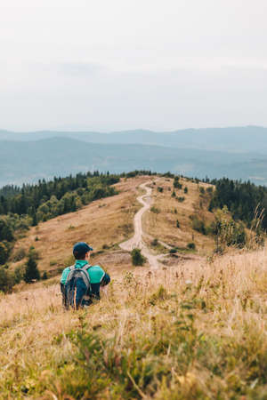 man with backpack hiking by autumn mountains
