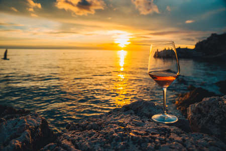 glass of wine at rocky sea beach on sunset