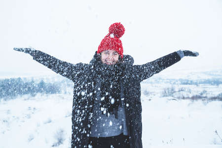 woman in red hat playing with snow outdoors
