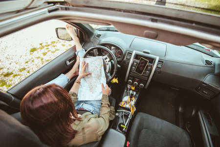 woman sitting in car checking map sea beach on background Banque d'images