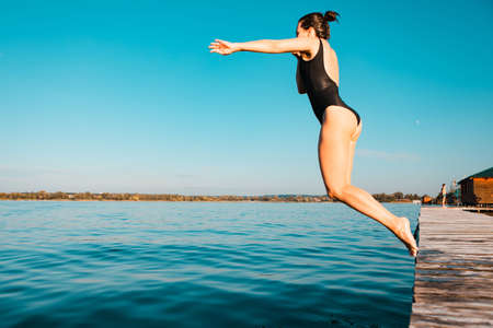 woman jumping from wooden pier in lake water