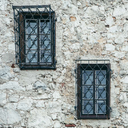 windows with metal shutters at gray stone building wall