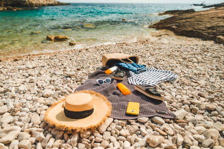 overhead view of beach stuff blanket with sun protection cream straw hat with bag