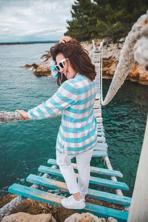 woman crossing suspension bridge sea on background
