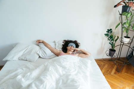 woman with sleeping mask in bed morning light through curtains