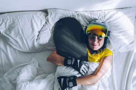 woman sleeping in bed with snowboard dreaming about ski at snow mountains Banque d'images