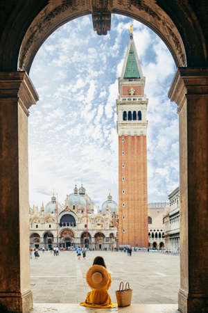 woman sitting on stairs resting looking at saint marco piazza at sunny summer day