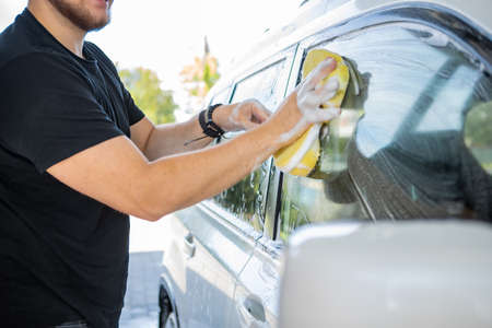 man cleaning car with yellow sponge. carwash concept
