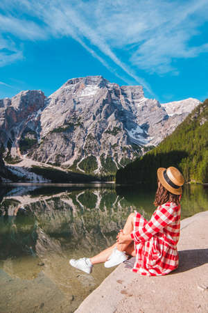 woman in red checkered dress with straw hat looking at mountain lake Banque d'images