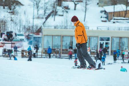 young man riding snowboard by winter hill