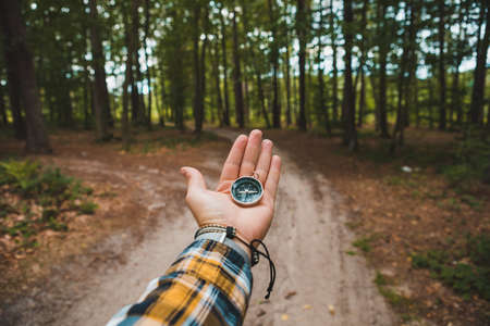 compass in man hand hiking by forest trail