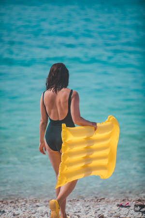 woman with yellow inflatable mattress walking to sea