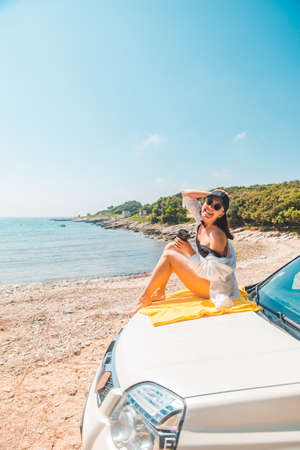 woman sitting at car hood drinking coffee enjoying view of the sea Banque d'images - 151399112