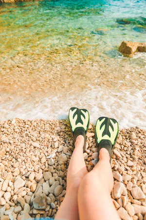 woman legs in flippers at beach sea on background