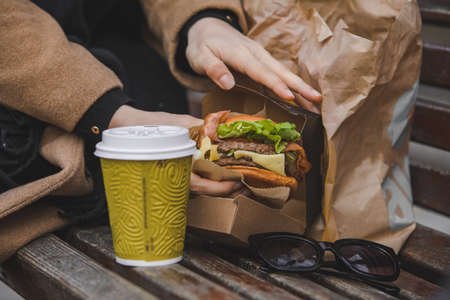 woman hands close up holding burger with coffee cup. fast food Banque d'images