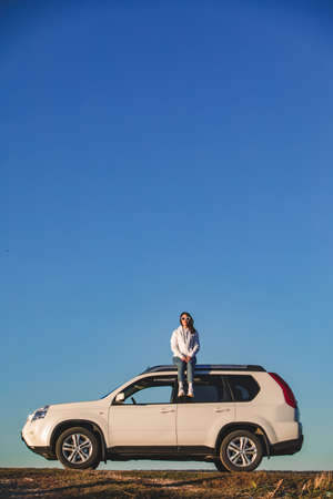 stylish woman in casual outfit sitting on the roof of the car at sunset