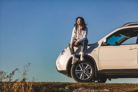 woman near white suv car enjoying sunset