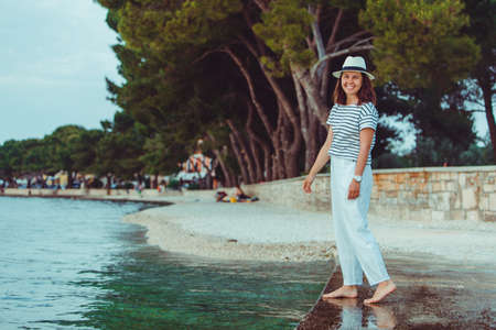 woman in white clothes and fedora hat walking by sea beach Banque d'images