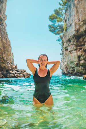 young sexy woman in black swimsuit at clear blue sea water Banque d'images