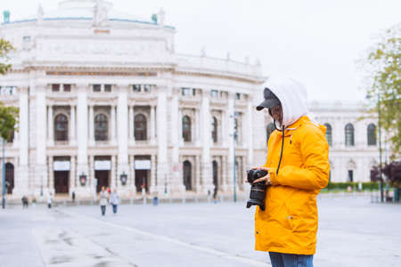 young pretty woman photographer with professional camera in front of old opera building