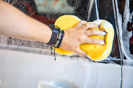 man hand holding yellow sponge cleaning car Banque d'images